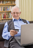 Senior shopping online. With laptop on sofa Stock Image