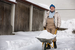 Senior Shovelling Snow Stock Image