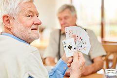 Senior shows a trump card at the card game. Tournament in the retirement home or at home royalty free stock images