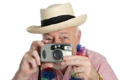 Senior Shutterbug. A senior man on vacation snaping photographs stock images