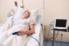 Senior sick woman recovering while wearing many medical devices stock images