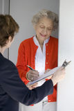 Senior signs a petition. Attractive senior woman signing a document at her front door Stock Photography