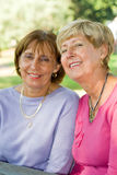 Senior sisters & friends. Portrait of two senior caucasian elegant women pose in the park on a sunny day. they are sisters and best friends stock photos