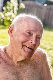 Senior sits in the chair in the garden Royalty Free Stock Photography