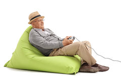 Senior sitting on a beanbag and playing videogames Royalty Free Stock Image