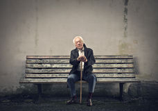 Senior sitting on a bench. Senior sitting on bench with a stick in his hands Stock Images