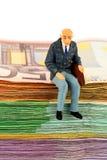 Senior sitting on bills Royalty Free Stock Image