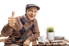 Senior sitting at a coffee table making a thumb up gesture Royalty Free Stock Photo