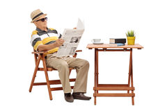 Senior sitting at a coffee table and reading a newspaper Royalty Free Stock Photography