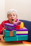 Senior sitting on the couch with gifts Stock Image