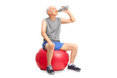 Senior sitting on a fitness ball and drinking water. Studio shot of a senior man sitting on a red fitness ball and drinking water isolated on white background Royalty Free Stock Photo