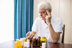 Senior sitting in front of medicine Stock Image