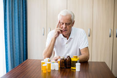 Senior sitting in front of medicine Royalty Free Stock Photo