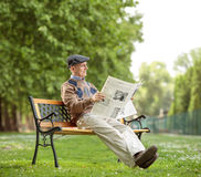Senior sitting reading a newspaper in the park. Senior sitting on a bench and reading a newspaper in the park Stock Photography