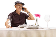 Senior sitting at restaurant table and talking on phone. Senior sitting at a restaurant table and talking on a phone isolated on white background Stock Photography