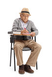 Senior sitting in a school chair and taking notes Royalty Free Stock Photos
