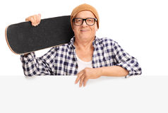Senior skater holding a skateboard behind a panel. Studio shot of a senior skater holding a skateboard and posing behind a blank panel isolated on white Royalty Free Stock Photos