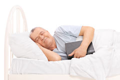 Senior sleeping in a bed and holding a book Stock Photo