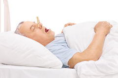 Senior sleeping with a clothespin on his nose. Senior sleeping in a bed and snoring with a clothespin stuck on his nose isolated on white background Royalty Free Stock Photos