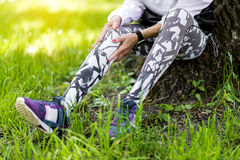 Senior slim lady resting in summer park after running Stock Image