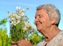 Senior smelling flowers. Stock Photo