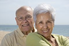 Senior smiling couple at the beach. Senior smiling couple with sea in the background Stock Image