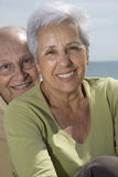 Senior smiling couple at the beach. Senior smiling couple with sea in the background Stock Photography