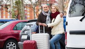 Senior smiling couple of travellers posing with trollers Stock Photo