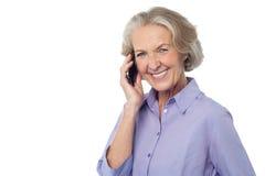 Senior smiling lady attending phone call stock photos