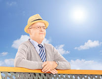 Senior smiling man on a bench posing outside Royalty Free Stock Images