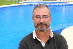 Senior smiling man vacation in blue pool happy Stock Photo