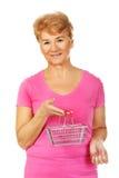 Senior smiling woman holding mini shopping basket Royalty Free Stock Images