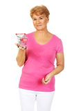 Senior smiling woman holding small trolley Stock Photo