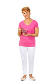 Senior smiling woman holding small trolley Royalty Free Stock Photography