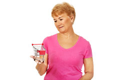 Senior smiling woman holding small trolley Royalty Free Stock Image