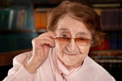 Senior smiling woman looking over the glasses. Selective focus. On vintage library background Royalty Free Stock Photography