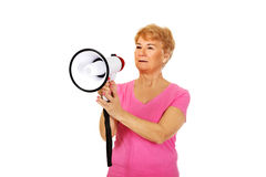 Senior smiling woman screaming through a megaphone Stock Photo