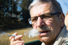 Senior smokes cigarette. Senior with glasses in nature smokes cigarette and blows smoke Stock Photo