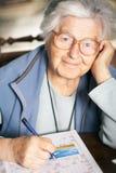 Senior solving crossword puzzle Stock Photo
