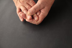 Senior with sore finger, copy space included. Man's hands on black background with copy space stock image
