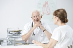 Senior specialist listening to patient. Senior medical specialist listening to patient`s problems during appointment in the hospital Royalty Free Stock Photography