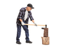 Senior splitting wood with an axe Royalty Free Stock Photo
