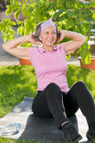 Senior sportive woman doing sit-ups sunny day Stock Photo