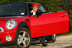 Senior in sports car. Senior in a red sports car (MINI Cooper royalty free stock images