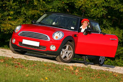 Senior in sports car. Senior in a red sports car (MINI Cooper stock image