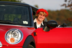 Senior in sports car. Senior in a red sports car (MINI Cooper royalty free stock photography