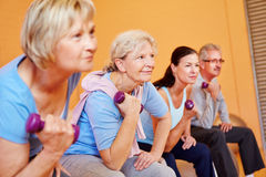 Senior sports in fitness center. Group of elderly people doing senior sports in fitness center with dumbbells Royalty Free Stock Image