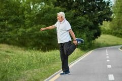 Senior sportsman doing stretching exercises on city`s racetrack. Keeping body fit, muscular, strong. Maintaining healthy lifestyle. Man wearing white polo Stock Image