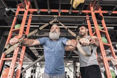 Senior sportsman with instructor are training in athletic center. Feeling confident. Low angle of concentrated old bearded men is doing push-ups in modern gym Royalty Free Stock Image