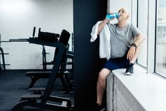 Senior sportsman resting and drink water. In gym stock photos